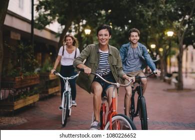 Tres jóvenes en bicicleta por la calle. Amigos masculinos y femeninos en la carretera con sus bicicletas.