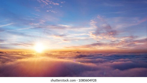 Schöner Sonnenuntergangshimmel über Wolken mit dramatischem Licht. Kabinenansicht vom Flugzeug