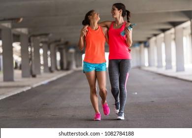 街道の高架下の街路をジョギングしている女性友達のカップル。ジョギングした後はリラックスして楽しんでいます。抱き合ってください。