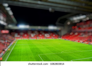 Blurred background of football stadium and soccer fans in match day on beautiful green field with sport light at the stadium.Sports,Athlete,People Concept.Mercy side,Anfield,Liverpool.