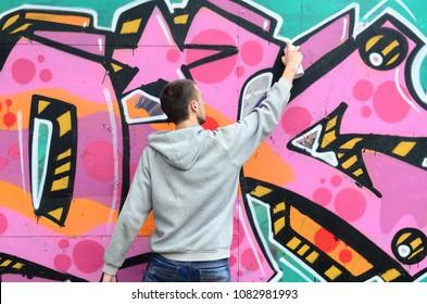 灰色のパーカーを着た若い男が雨天時に壁にピンクと緑の色で落書きを描く