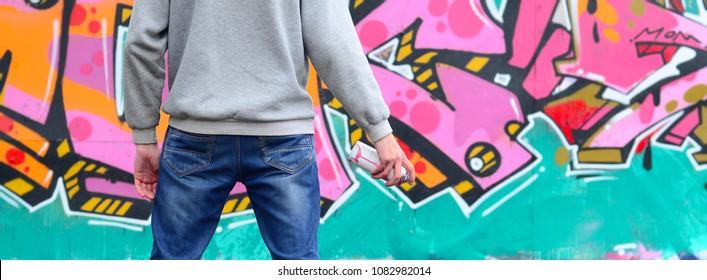 灰色のパーカーを着た若いグラフィティアーティストが、雨天の壁にピンクとグリーンのグラフィティを置いて壁を見ています。ストリートアートのコンセプト
