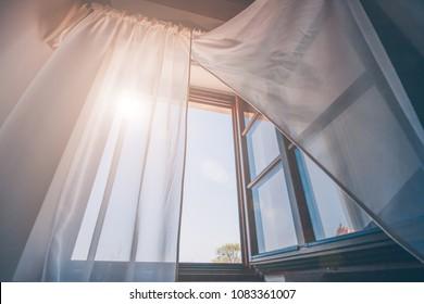 Helle Morgensonne im offenen Fenster durch die Vorhänge
