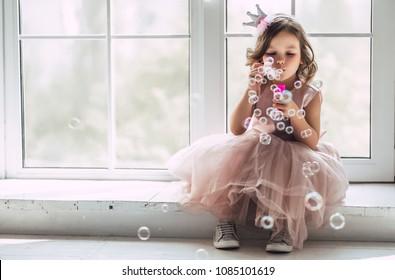 Kleines süßes Mädchen im schönen Kleid sitzt in der Nähe des Fensters zu Hause und bläst Seifenblasen.