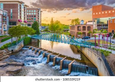 米国サウスカロライナ州グリーンビルの夕暮れ時のリーディ川沿いのダウンタウンの街並み。