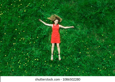 Beautiful girl lies on the grass in nature and smiles. Top view. Long shot. Summer concept.