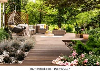 Hermosa terraza de madera con muebles de jardín rodeada de vegetación en un cálido día de verano