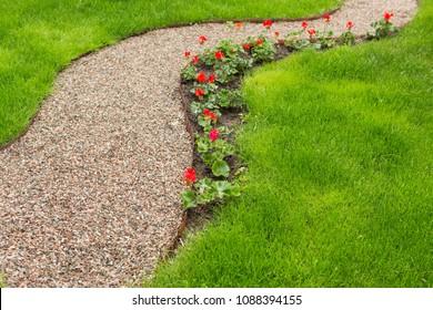 voetpad van klein grind in de tuin, langs het bloembed met rode bloemen, groen gras, selectieve focus