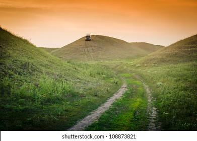 SUV en las verdes colinas cubiertas de hierba en la noche