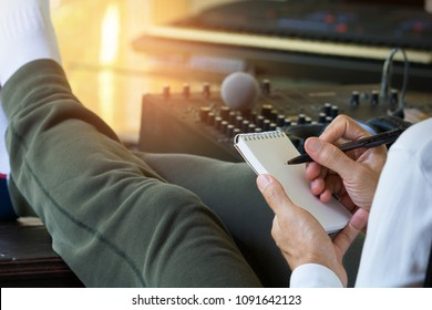 Male sound engineer hipster producer laying his feet up on old wooden console writing a paper note.Music producer working in home recording studio.