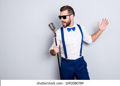 Portret zgodne atraktivne pjevačice u plavim hlačama s vešalicama i crnim naočalama, pjevajući hit s otvorenim ustima u mikroskopu gestom rukom izoliranom na sivoj pozadini