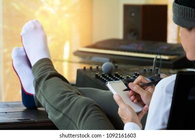 Männlicher Toningenieur-Hipster-Produzent, der seine Füße auf alte Holzkonsole legt, die eine Papiernotiz schreibt. Musikproduzent, der im Hauptaufnahmestudio arbeitet.