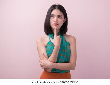 ピンクの背景に分離された色のカジュアルなドレスの思考と想像力でかわいいアジアの女性