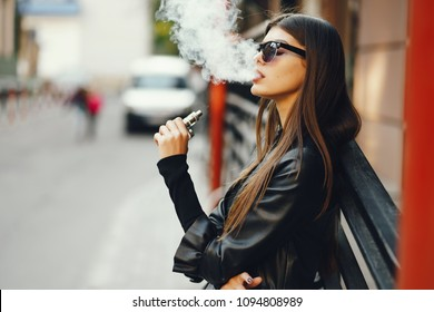 彼女は街を歩いているときに電子タバコを吸うスタイリッシュな女の子