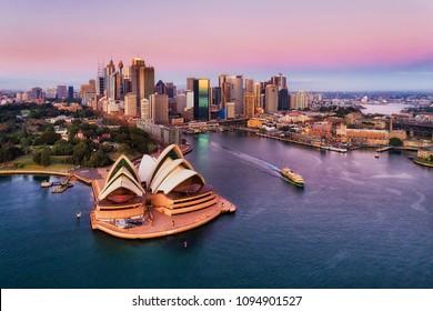 Rosa bunter Sonnenaufgang über Sydney City CBD am Ufer des Hafens um Circular Quay mit wichtigen architektonischen Wahrzeichen und Symbolen von Australien.
