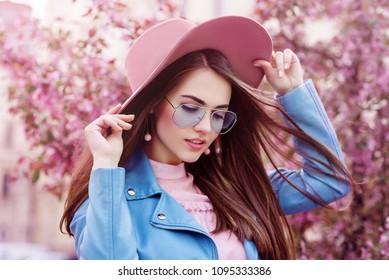 Junges schönes modisches Mädchen, das stilvolle blaue Fliegersonnenbrille, rosa Wildlederhut, Ohrringe, Bikerjacke trägt. Modell, das in der Straße mit blühenden Bäumen aufwirft. Frühlingsmode-Konzept.