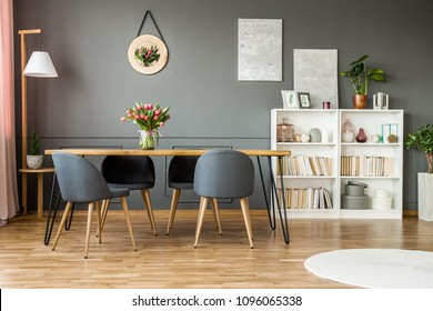 Estante de madera blanca con libros, decoración y plantas frescas de pie en el interior del comedor gris con flores en la mesa de horquilla