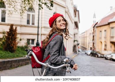 Riendo a chica de pelo oscuro rizado mirando hacia atrás, de pie en la calle vieja en la mañana. Bastante jovencita con mochila de cuero posando con bicicleta, esperando amigo en la avenida.