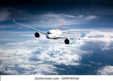 Avión de pasajeros en vuelo. El avión vuela alto en el cielo azul sobre las nubes. Vista frontal. Tacón derecho.