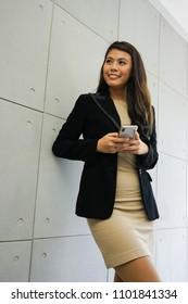 Porträt der Geschäftsfrau. Eine Geschäftsfrau lehnt sich mit ihrem Handy an die Wand.