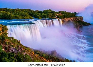 Niagara falls in the summer during beautiful evening, night with clear dark sunset blue sky. Niagara fall water hit with many colorful lights that is beautiful in a way. Sky turning dark and cold.