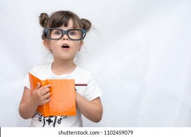 Überraschtes süßes Kind in Brille, mit Bleistift in Notizbuch schreibend, Mund weit offen haltend. Vier oder fünf Jahre altes Kind, isoliert auf Weiß, Platz für Werbetext