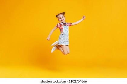 Niña niño gracioso saltando sobre un fondo amarillo de color