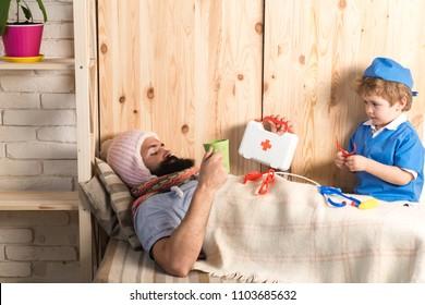 Kind und Vater spielen Krankenhaus. Patient mit Grippe im Bett unter Wolldecke liegen. Doktor, der kranken bärtigen Mann zu Hause, Lernspielkonzept besucht.