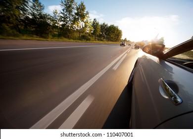 Autofahrt auf der Straße bei sonnigem Wetter, Bewegungsunschärfe