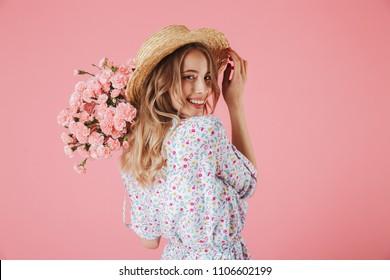 Cerrar el retrato de una mujer joven atractiva en vestido de verano y sombrero de paja con ramo de claveles y mirando por encima del hombro aislado sobre fondo rosa