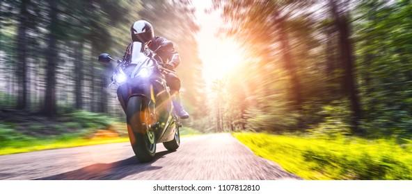 moto en el camino forestal a caballo. divirtiéndose conduciendo por la carretera vacía en un viaje en motocicleta. copyspace para su texto individual.