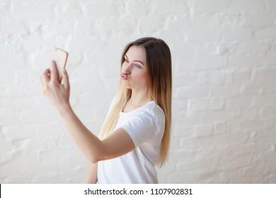 ブルネットの髪のスタイルの女性が彼女のスマートフォンでいちゃつく