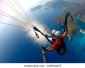 Gleitschirmfliegen am Himmel. Gleitschirm-Tandem, der über Meer mit blauem Wasser und Bergen an hellem sonnigem Tag fliegt. Luftaufnahme des Gleitschirms und der blauen Lagune in Oludeniz, Türkei. Extremsport. Landschaft