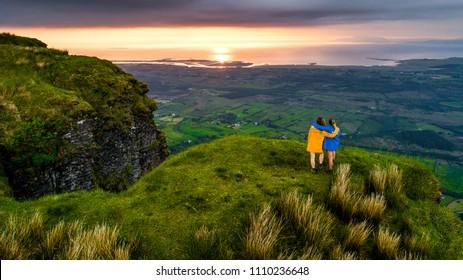 アイルランドの夏の曇りの日にレインジャケットを1つ黄色、もう1つを青で山でハイキングする2人の女性。山でのハイキング。