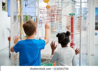 Zwei Kinder, die eine Wissenschaftsausstellung betrachten, Rückansicht