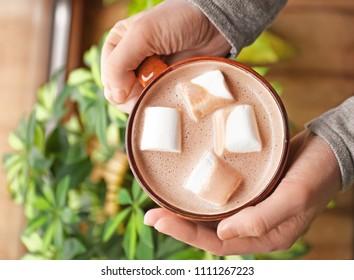 Mujer sosteniendo una taza de cacao aromático con malvaviscos, vista superior