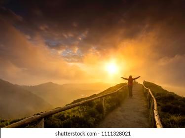 Vrouw stond op een prachtig pad met open armen bij de zonsondergang