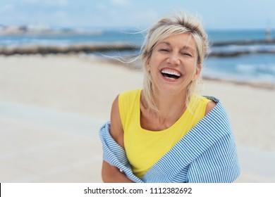 Lachende lebhafte blonde Frau mit einem Sinn für Humor, die auf einem tropischen Strand mit Kopienraum steht