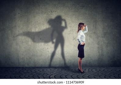 Vista lateral de una mujer de negocios imaginando ser un superhéroe que parece aspirado.