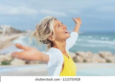Freudige Frau, die die Freiheit des Strandes genießt, der mit offenen Armen und einem glücklichen Lächeln steht, das zum Himmel aufblickt