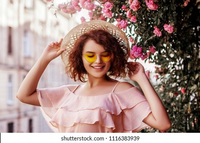 Outdoor close up portrait of young beautiful happy smiling curly girl wearing stylish yellow sunglasses, straw hat, pink blouse with ruffles. Model posing near blooming roses. Summer fashion concept