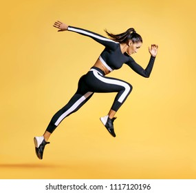 Sporty woman runner in silhouette on yellow background. Photo of attractive woman in fashionable sportswear. Dynamic movement. Side view. Sport and healthy lifestyle