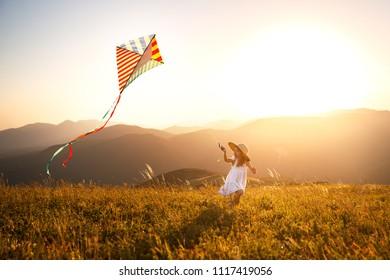 niña niño feliz corriendo con una cometa al atardecer al aire libre