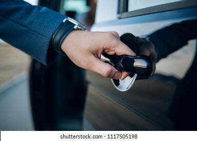ハンドルを渡してください。車のドアを開ける正装の男のクローズアップ