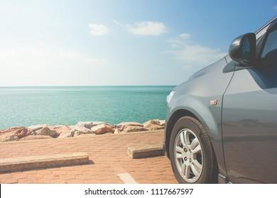 夏休みと休日のコンセプト:海と青い空を背景にビーチ近くの海岸の駐車場に駐車した車。
