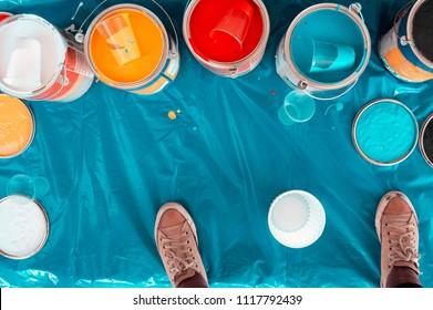 Vista superior de muchos cubos y contenedores de pintura de colores sobre una superficie de plástico turquesa y un par de zapatos marrones