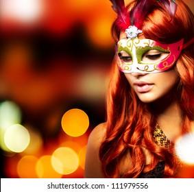 仮面舞踏会。休日の点滅する背景の上のカーニバルマスクの美しい少女。ボケ