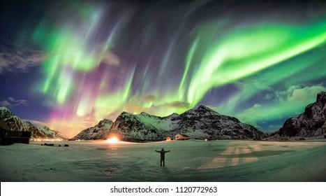 Aurora borealis (Nordlichter) über Berg mit einer Person am Strand von Skagsanden, Lofoten, Norwegen