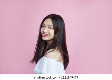 Schöne Frau, Jugend, Glück, positives, lächelndes Gesicht, glückliche Augen, süßes Lächeln, schwarzes Haar, Asien, chinesisches Aussehen, weiße lässige Bluse, rosa Hintergrund, Aktivität, in Bewegung