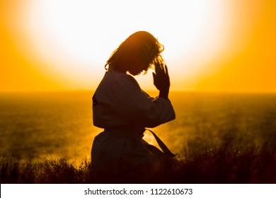 Silhouette eines Samurai in einem Kimono beim Meditieren an der Ozeanküste bei Sonnenaufgang. Das Konzept eines gesunden Lebensstils, Einheit mit der Natur, Meditation.